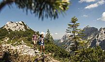 Austria, Tyrol, Tannheimer Tal, young couple hiking on mountain trail - UUF005071