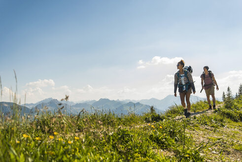 Austria, Tyrol, Tannheimer Tal, young couple hiking on mountain trail - UUF005076