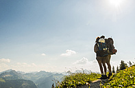 Austria, Tyrol, Tannheimer Tal, young couple standing on mountain trail looking at view - UUF005081