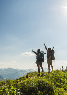 Austria, Tyrol, Tannheimer Tal, cheering young couple standing on mountain trail looking at view - UUF005084