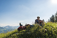 Austria, Tyrol, Tannheimer Tal, young couple resting on alpine meadow - UUF005099