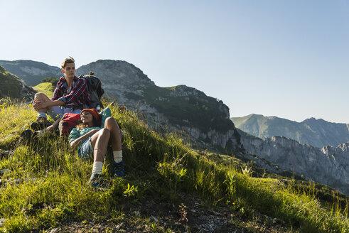 Austria, Tyrol, Tannheimer Tal, young couple resting on alpine meadow - UUF005104