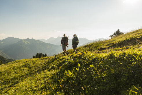 Austria, Tyrol, Tannheimer Tal, young couple hiking on alpine meadow in backlight - UUF005110