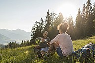 Austria, Tyrol, Tannheimer Tal, young couple resting on alpine meadow - UUF005117