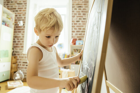 Little boy drawing on chalk board in children's room - MFF002066
