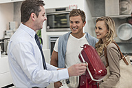 Shop assistant talking to young couple shopping kitchen equipment - ZEF007062