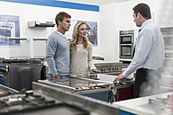 Shop assistant talking to young couple shopping kitchen equipment - ZEF007074