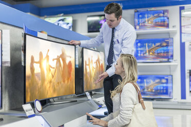 Shop assistant showing flatscreen TV to customer - ZEF007091