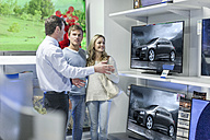 Shop assistant showing flatscreen TVs to young couple - ZEF007346