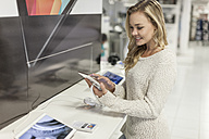 Young woman testing digital tablet in a shop - ZEF007476