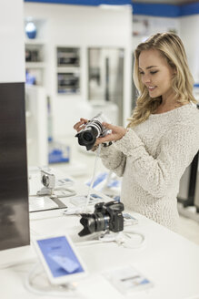 Young woman examining a camera in a shop - ZEF007348