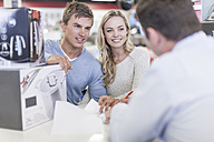 Young couple at counter in shop paying for purchase - ZEF007352