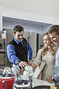 Shop assistant talking to young couple shopping kitchen equipment - ZEF007359