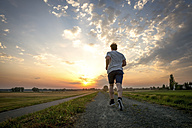 Rear view of man jogging at sunset - PUF000392