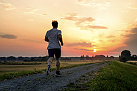 Rear view of man jogging at sunset - PUF000389