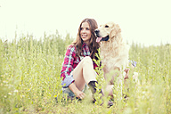 Woman and her Golden Retriever sitting on a meadow - MAEF010820