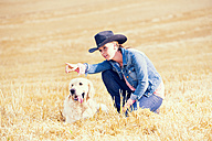Young woman and Golden Retriever sitting on a stubble field - MAEF010822