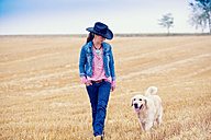 Young woman and Golden Retriever walking on a stubble field - MAEF010824