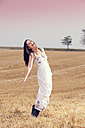 Laughing young woman on a stubble field - MAEF010828