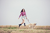 Young woman and her Golden Retriever at a field - MAEF010835