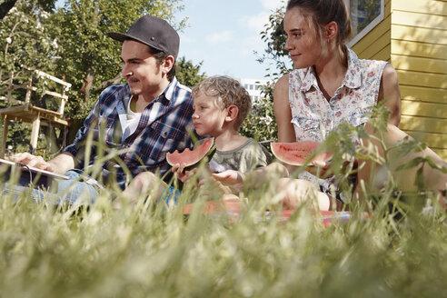 Family in garden eating watermelon slices - RHF000997