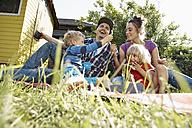 Happy family relaxing in garden - RHF001009