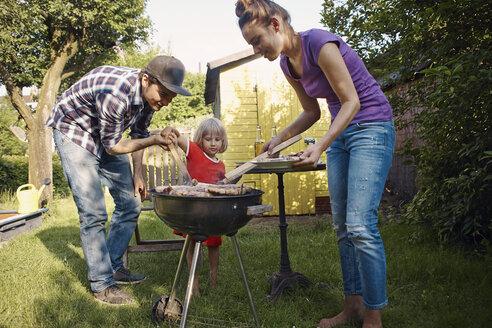 Family having a barbecue in garden - RHF001037