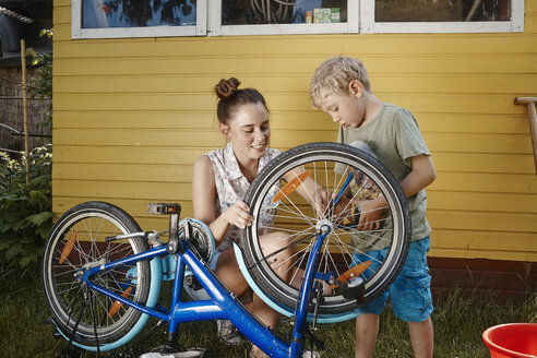 Mother and son repairing bicycle together - RHF001026