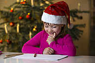 Little girl with Christmas cap looking at her Christmas list - ROMF000122