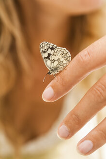Butterfly on woman's hand - TCF004776
