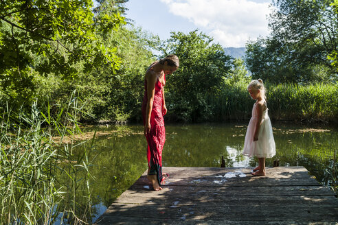 Woman with wet dress and daughter on jetty at a lake - TCF004780
