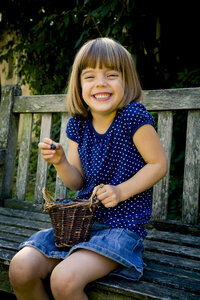 Grinning little girl sitting on a garden bench with wickerbasket of blueberries - LVF003736