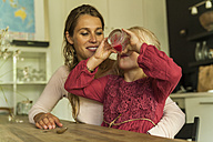 Mother looking at daughter drinking from glass - TCF004797