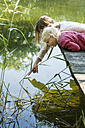 Mother and daughter lying on jetty at a lake looking at water - TCF004798
