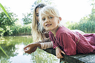 Mother and smiling daughter lying on jetty at a lake - TCF004803
