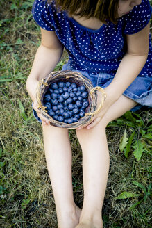 Little girl sitting on a meadow with wickerbasket of blueberries - LVF003740