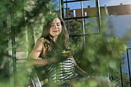 Young woman on balcony drinking morning coffee - RIBF000156