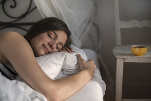 Young woman lying in bed, embracing pillow - RIBF000162