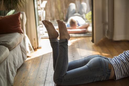 Young woman at home lying barefoot on wooden floor, low section - RIBF000244