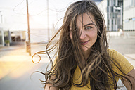 Germany, Cologne, portrait of smiling young woman with blowing hair - RIBF000212