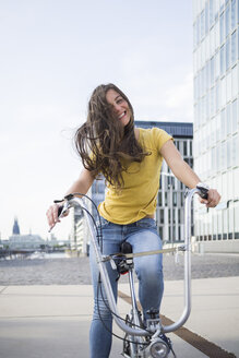 Germany, Cologne, portrait of smiling young woman with blowing hair on her bicycle - RIBF000215