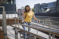 Germany, Cologne, young woman with bicycle looking at her smartphone - RIBF000229