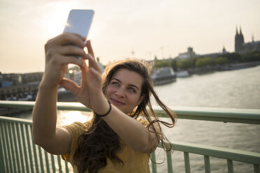 Germany, Cologne, young woman standing on Rhine bridge taking a selfie with her smartphone - RIBF000230