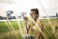 Germany, Cologne, young woman drinking beer out of a bottle on a meadow near Rhine River - RIBF000223