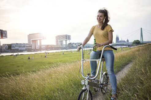 Germany, Cologne, young woman with bicycle on meadow near Rhine River at evening twilight - RIBF000226