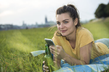 Germany, Cologne, woman with beer bottle and smartphone relaxing on a meadow at evening twilight - RIBF000245