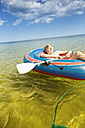 Germany, Niendorf, young boy relaxing in an inflatable boat - MEMF000902