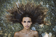 Portrait of a  woman lying on a rock with tousled hair - RAEF000252