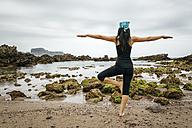 Spain, Asturias, Gijon, woman doing yoga on a rocky beach - MGOF000391