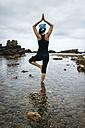 Spain, Asturias, Gijon, woman doing yoga on a rocky beach - MGOF000376